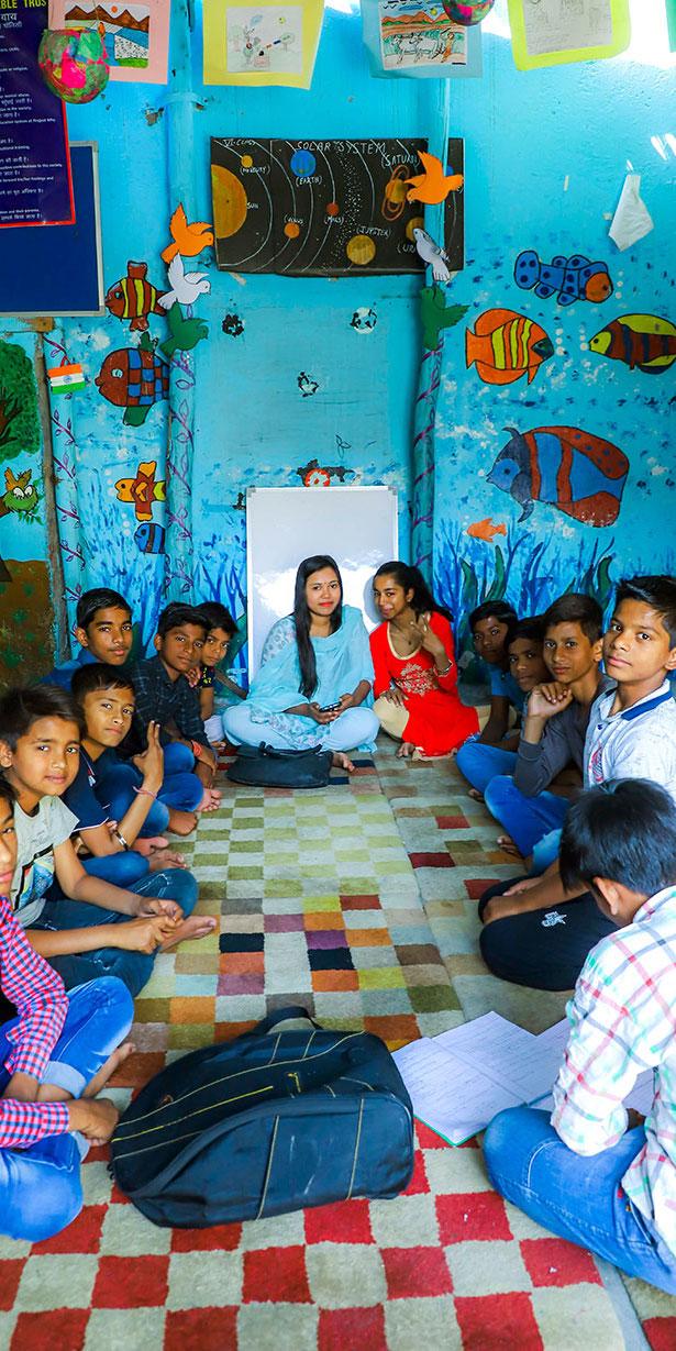 Des petits indiens écoutent attentivement leur deux professeurs au centre de l'association Project Why