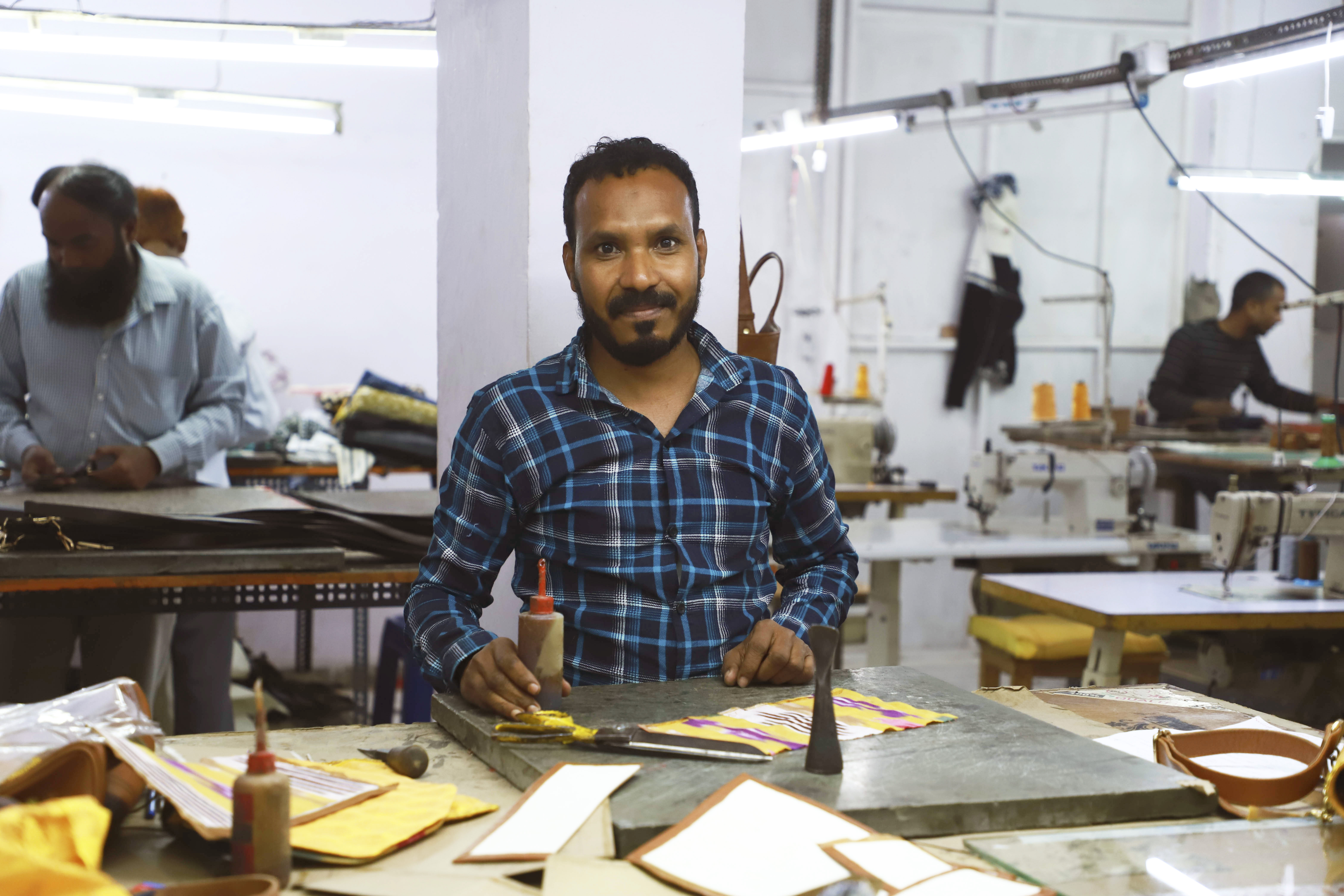 Un artisan indien souriant qui travaille sur le sac bandoulière jholi