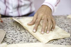 Gros plan sur la main d'un artisan de la marque jholi en train de tenir la doublure des pochettes